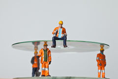 Miniature people in action with CDs Royalty Free Stock Photos