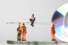 Miniature people in action with CDs Stock Photos