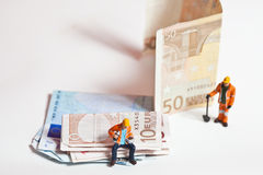 Miniature people in action with euro banknotes Stock Image