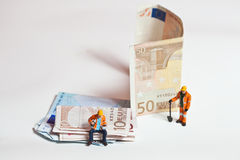 Miniature people in action with euro banknotes Royalty Free Stock Images