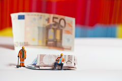 Miniature people in action with euro banknotes Stock Photography