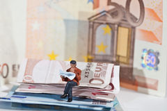 Miniature people in action with euro banknotes Royalty Free Stock Image
