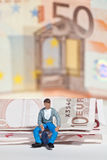 Miniature people in action with euro banknotes Stock Photo