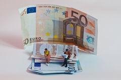 Miniature people in action with euro banknotes Royalty Free Stock Photo