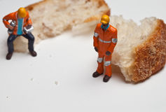 Miniature people in action with a piece of bread Royalty Free Stock Photos