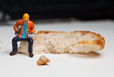 Miniature people in action with a piece of bread Royalty Free Stock Photography