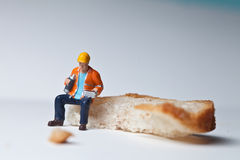 Miniature people in action with a piece of bread Stock Photos