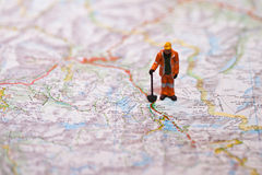 Miniature people in action on a roadmap Royalty Free Stock Photos