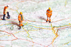 Miniature people in action on a roadmap Stock Photo