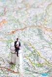 Miniature people in action on a roadmap Stock Photography