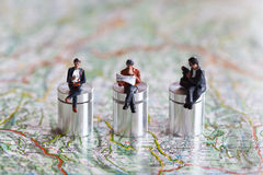 Miniature people in action on a roadmap. Miniature people in action in various situations Royalty Free Stock Photos