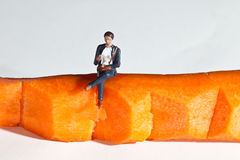 Miniature people in action sitting on a carrot Royalty Free Stock Photos