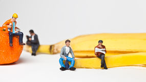 Miniature people in action stting on a banan Stock Photo