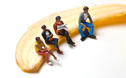 Miniature people in action stting on a banan Stock Photography
