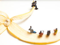 Miniature people in action stting on a banana Stock Photos
