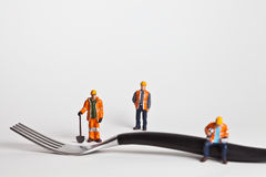 Miniature people in action worker on a fork Stock Images
