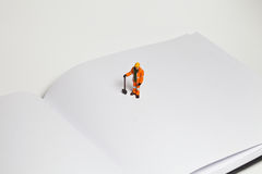 Miniature people in action worker on an open book Stock Image