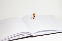 Miniature people in action worker on an open book Royalty Free Stock Images
