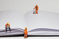 Miniature people in action worker on an open book Royalty Free Stock Photography
