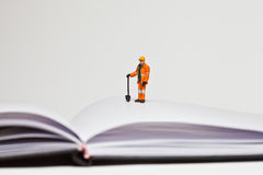 Miniature people in action worker on an open book Stock Photos