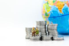 Miniature people, adult couple figure standing on top of stack coins . Image use for background retirement planning, Life Stock Photography