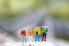 Miniature people: backpacker celebrating success standing on top royalty free stock images