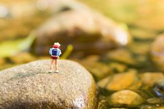 Miniature people, backpackers walking on the stones at river. Travel Lifestyle adventure vacations concept. Miniature people, backpackers walking on the stones Royalty Free Stock Photo