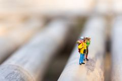 Miniature people, backpackers walking on the stones at river. Travel Lifestyle adventure vacations concept.  Royalty Free Stock Image