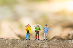 Miniature people, backpackers walking on the stones at river. Travel Lifestyle adventure vacations concept.  Royalty Free Stock Images