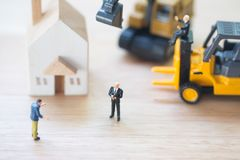 Miniature people : Banker seize asset. Forced eviction and confiscation. Clarification of ownership of property. Concept settlement of litigation stock photos