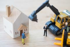 Miniature people : Banker seize asset. Forced eviction and confiscation. Clarification of ownership of property. Concept settlement of litigation royalty free stock photography