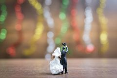 Miniature people bride and groom  on wooden floor with colorful Royalty Free Stock Image