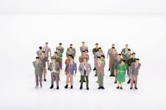Miniature people business standing in straight lines over white. Backdrop or background Royalty Free Stock Photo