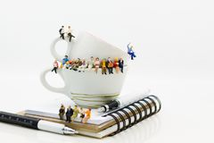 Miniature people : Business team sitting on book and having a coffee break. Image use for business concept.  stock photography