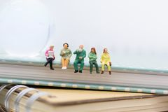 Miniature people : Business team sitting on book and having a coffee break. Image use for business concept.  royalty free stock image