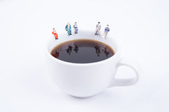 Miniature people business team sitting on white coffee cup. Having a coffee break. business idea concept Stock Photos