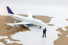 Miniature people: Business team standing in front of airplane. B Royalty Free Stock Images