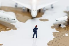 Miniature people: Business team standing in front of airplane. B Royalty Free Stock Image