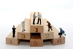 Miniature people: Businessman climbing up challenging career ladder Royalty Free Stock Image