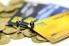 Miniature people : businessman with credit card and stack coins,commitment, agreement, investment, business and partnership. Concept royalty free stock image