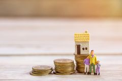 Miniature people: Businessman and family standing with step of c. Oins and toy house. Concept of Financial and money.Office desk with money coins and business stock image