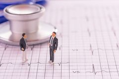 Miniature people : Businessman figures standing on the cardiovas. Cular medical exam paper and closeup stethoscope background. Business and healthy concept. copy Stock Image