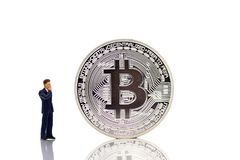 Miniature people : businessman looking for find money with bitcoin. Miniature people : businessman looking for find money with bitcoin, using as business Royalty Free Stock Photo