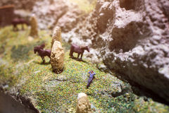 Miniature people: businessman lying on the meadow next to glazing horses. Nature eco relax concept. Royalty Free Stock Image