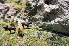Miniature people: businessman lying on the meadow next to glazing horses. Nature eco relax concept. Royalty Free Stock Photo