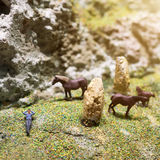 Miniature people: businessman lying on the meadow next to glazing horses. Nature eco relax concept. Stock Images