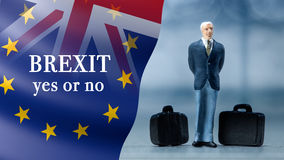 Miniature people – a businessman posing with United Kingdom and European union flags combined for the 2016 referendum Royalty Free Stock Photos