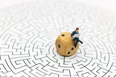 Miniature people: Businessman reading on center of maze. Concept Royalty Free Stock Image