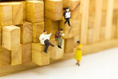 Miniature people: businessman reading newspaper on wooden block. Image use for background education or business concept.  royalty free stock image