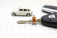 Miniature people : Businessman sitting on car key. Image use for Advertising product in the market today, competition on the. Business trading royalty free stock images